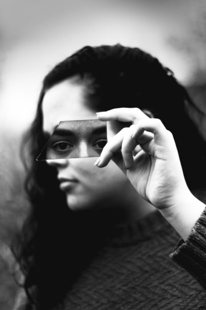 black and white image of a woman with her head turned holding a broken mirror over her eyes. A man's eyes are reflected in the mirror.